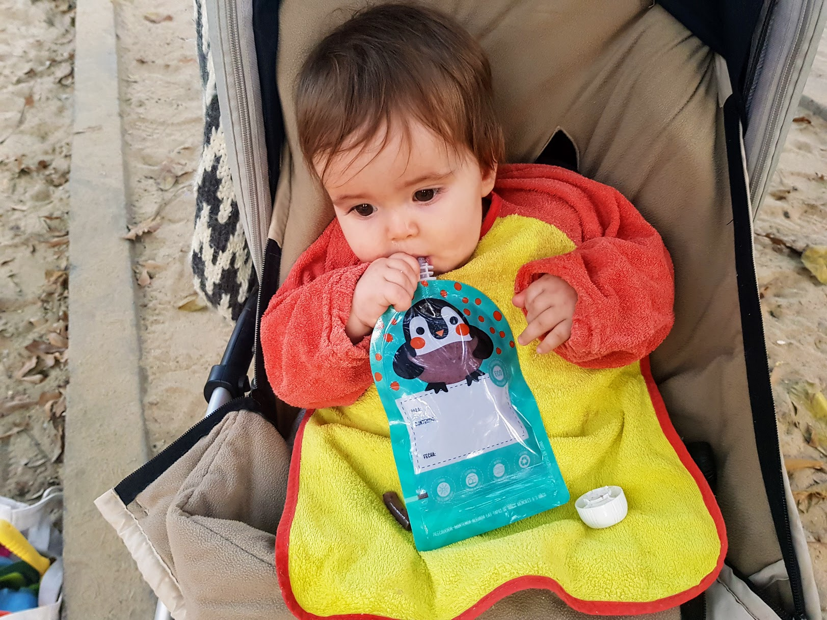 baby with reusable food pouch
